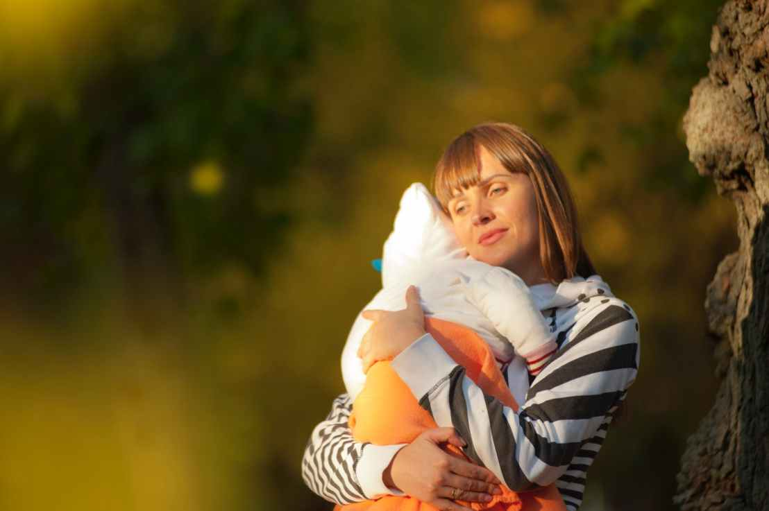 selective focus photo of woman carrying baby